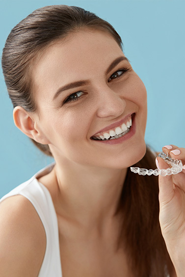 woman smiling while holding invisible braces aligners